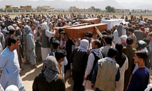 Men carry coffins of the victims of a blast at a wedding in Kabul.