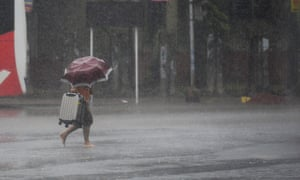 A man makes his way under heavy rain in Khulna, southern Bangladesh.