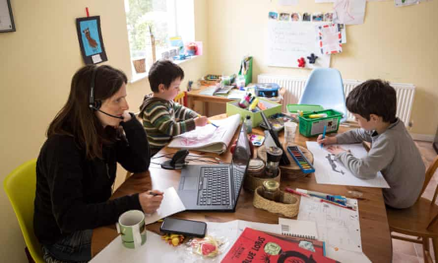 Leo (R) and his brother Espen (C) complete homeschooling activities as their mother Moira works from home in the village of Marsden, near Huddersfield