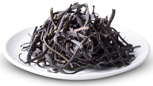A white plate with a tangle of black tagliatelle-type pasta