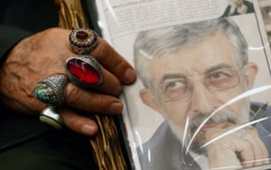 An older man clutches a photo of Gholam Ali Haddad Adel.