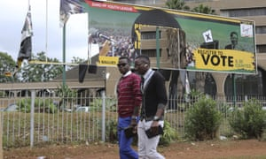 People walk past a partly torn Mugabe banner outside the Zanu-PF headquarters in Harare