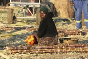 Harare, Zimbabwe A woman sits on a bunch of sugarcane while waiting for transport at a market place. Many Zimbabweans are bracing themselves for fresh unrest later this week after the main opposition party called for renewed public rallies