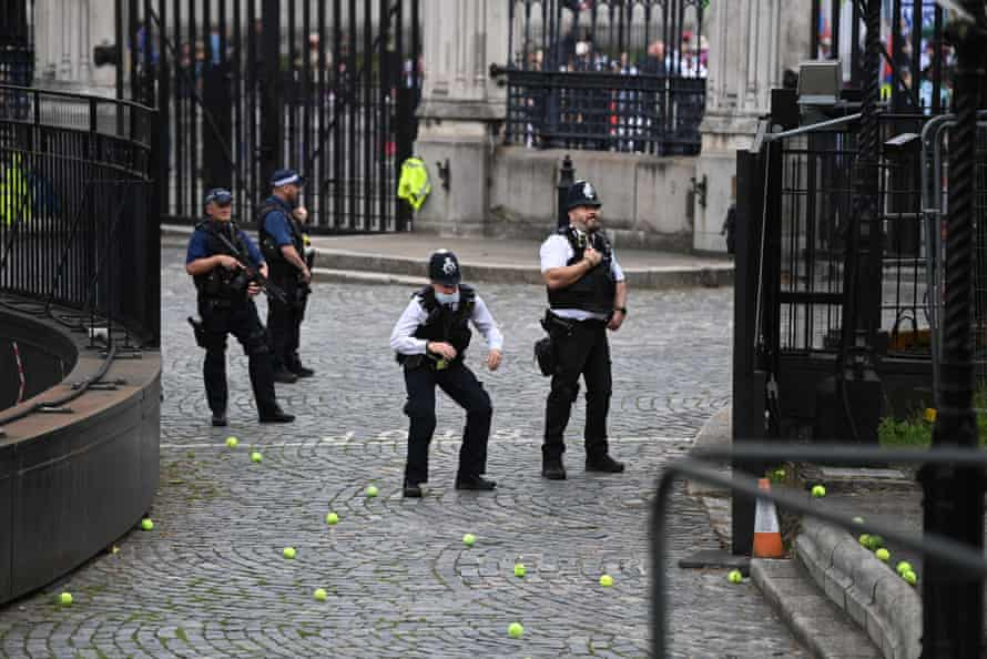 A policeman ducks as protestors throw tennis balls over fences around the Houses of Parliament.