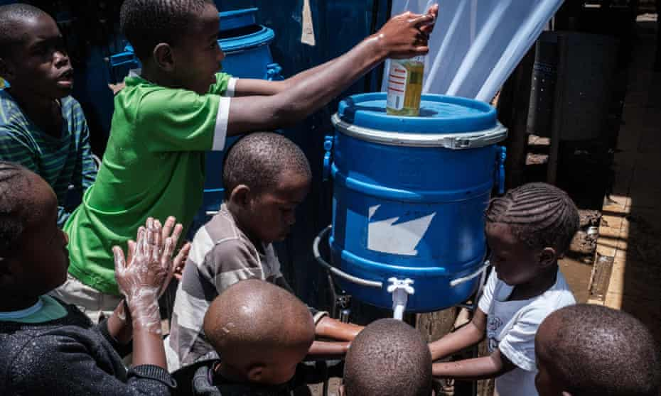 Children learn how to wash hands to prevent the spread of Covid at one of the hand washing stations installed by local NGO Shining Hope for Communities (Shofco) at Kibera slum in Nairobi, March 2020