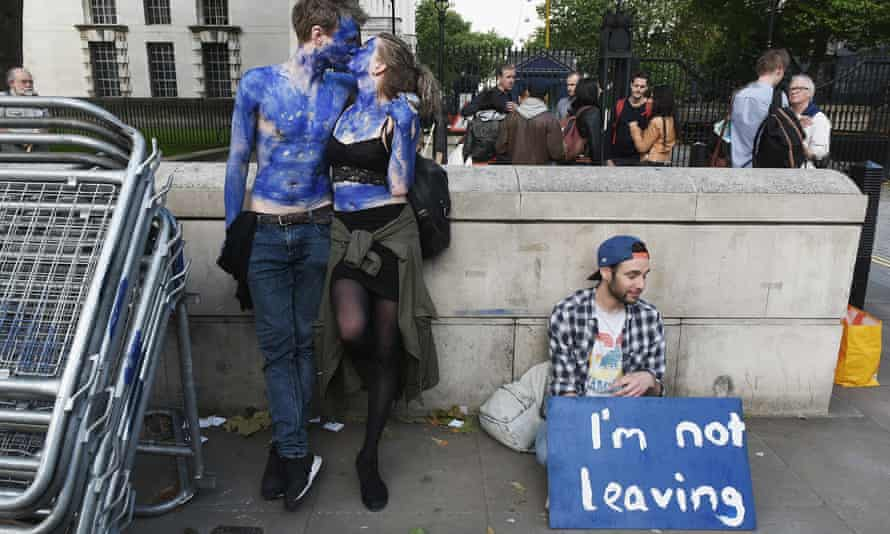 A young couple painted as EU flags and man with a sign saying 'I'm not leaving',  protest outside Downing Street.