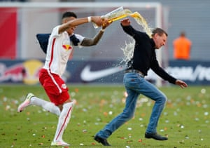 Davie Selke showers RB Leipzig head coach Ralf Rangnick with beer while celebrating promotion to the top flight.