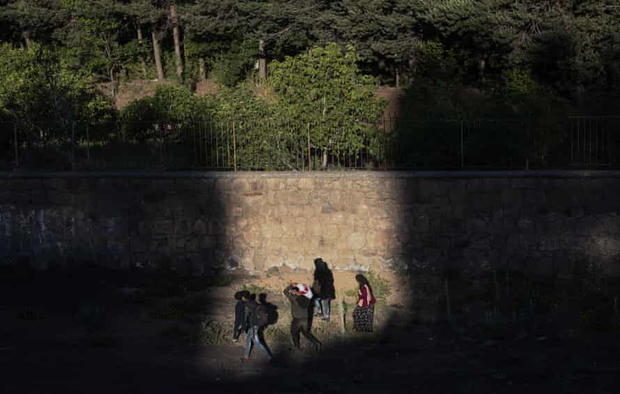 A group of people walk at sunset next to a railway in Van city after crossing the Iran-Turkey border, on 8 June 2021.
