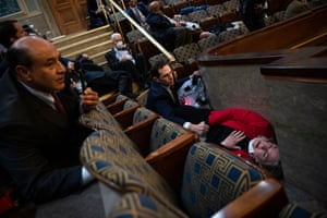 Washington DC, US – Representative Jason Crow, of Colorado, comforts fellow Democrat Susan Wild, of Pennsylvania, while taking cover as protesters disrupted the joint session of Congress to certify the electoral college vote.