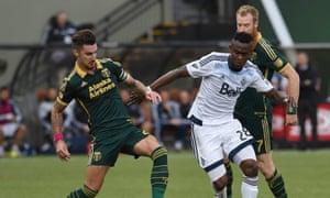 Portland's Liam Ridgewell holds off Vancouver Whitecaps midfielder Gershon Koffie.
