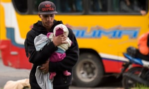 A Venezuelan migrant carries a baby at an improvised camp near a bus terminal in Bogotá, Colombia