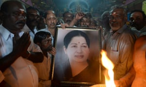 Supporters hold a photograph of Jayalalithaa Jayaram.