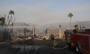 Firefighters hose down hot spots on a wildfire-ravaged property in Malibu, California.
