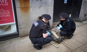 Police officers assist a man who is high after taking spice on the edge of Piccadilly Gardens in Manchester.