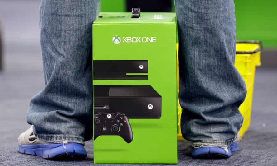A man stands over his new Xbox One console.
