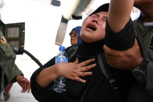 A woman cries as she waits to be evacuated.