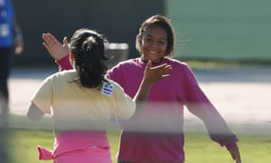 Two girls give high-fives as they play soccer at the Homestead shelter. But there are plentiful reminders that the site is not a summer camp.