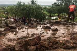 People in Chiluvi, a village in central Mozambique, walk along a flooded, muddy street.