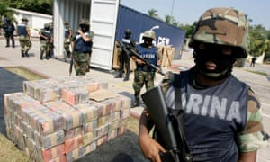 A marine stands guard near packs of cocaine at a naval base in Manzanillo.