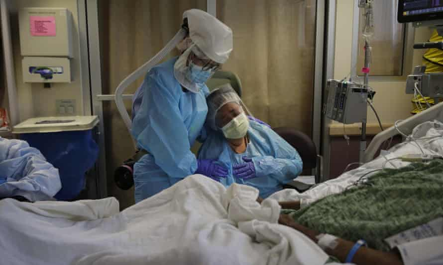 A woman is comforted by a health worker as she sits at the bedside of her husband at a Covid unit in Fullerton, California, on 31 July 2020.