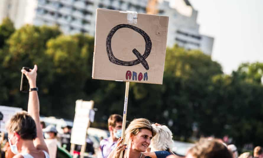 A protester holds a QAnon sign at a demonstration in Germany