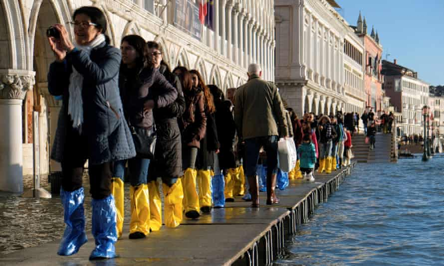 Tourists walk in St Mark's Square during high tide in Venice.