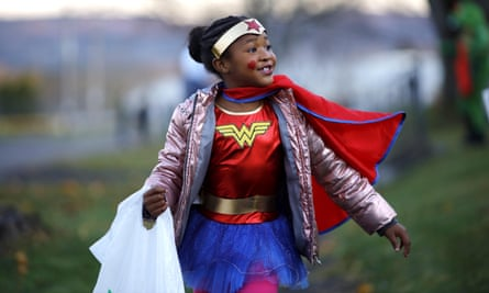Wonder Woman, also known as Timya Garett, seven, trick-or-treats from house to house on New Hampshire Avenue on 2 November 2019.