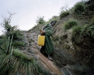 Uchiya Nallo, eight months pregnant, gathering water to make the beer for the village men to celebrate her birth Konso region, Ethiopia 2013