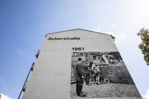 A photograph showing the construction of the Berlin Wall on the side of a building