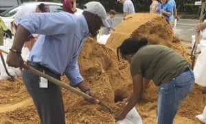 Tallahassee Mayor Andrew Gillum, left, helps Eboni Sipling fill up sandbags on Monday in Tallahassee, Florida.