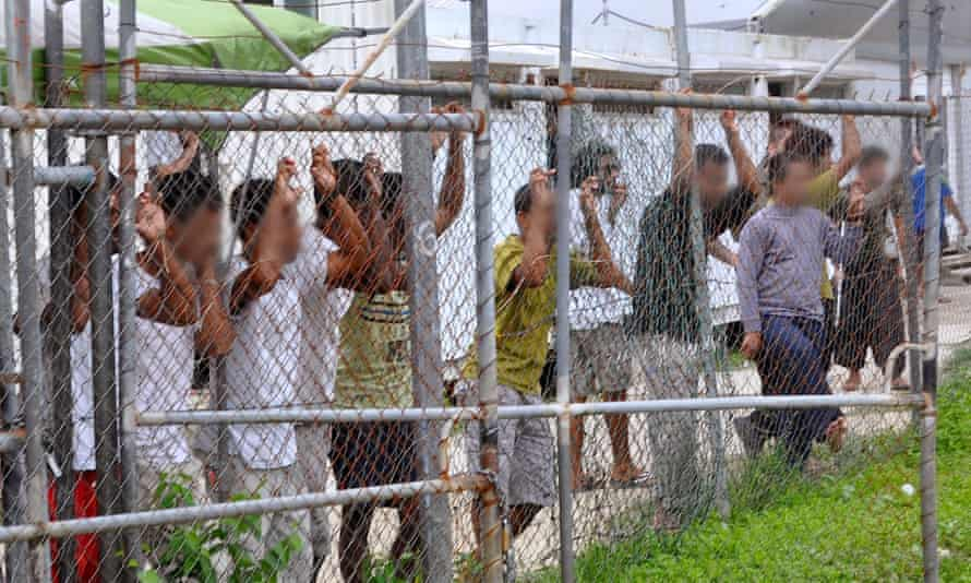 Asylum-seekers look through a fence at the Manus Island detention centre in Papua New Guinea March 21, 2014.