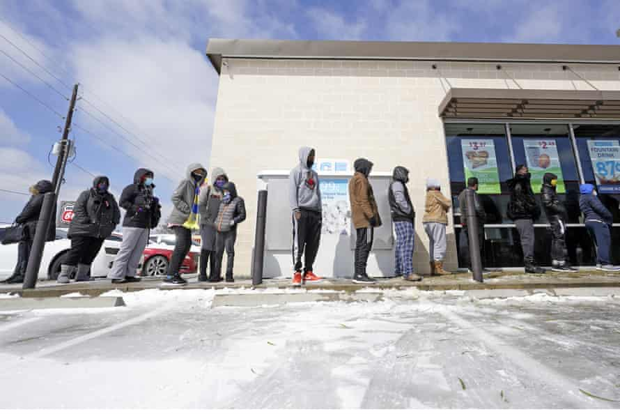 People wait in line to purchase groceries on Monday in Houston.
