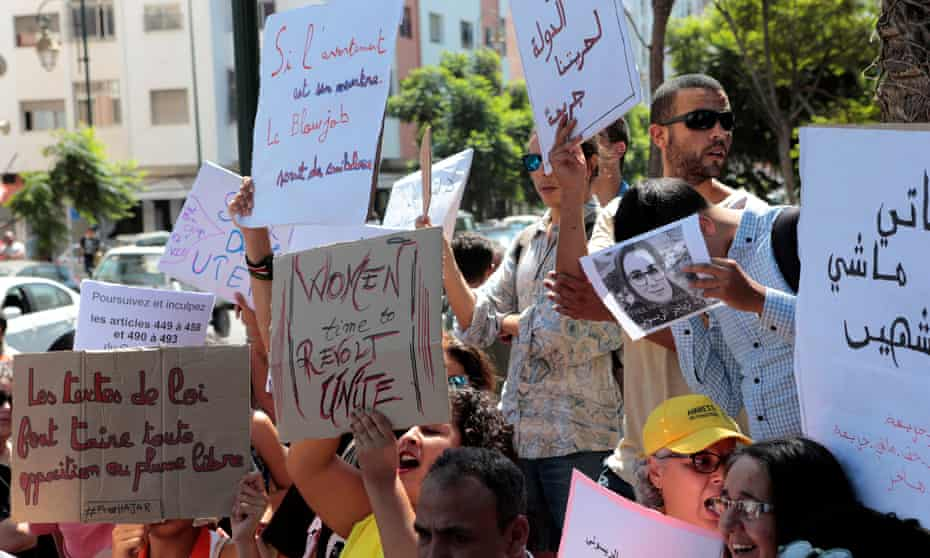 Activists hold signs in solidarity with Hajar Raissouni during a protest outside the Rabat tribunal.