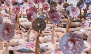 People pose nude holding cut outs of nipples during a photo shoot by the artist Spencer Tunick on Monday in New York.