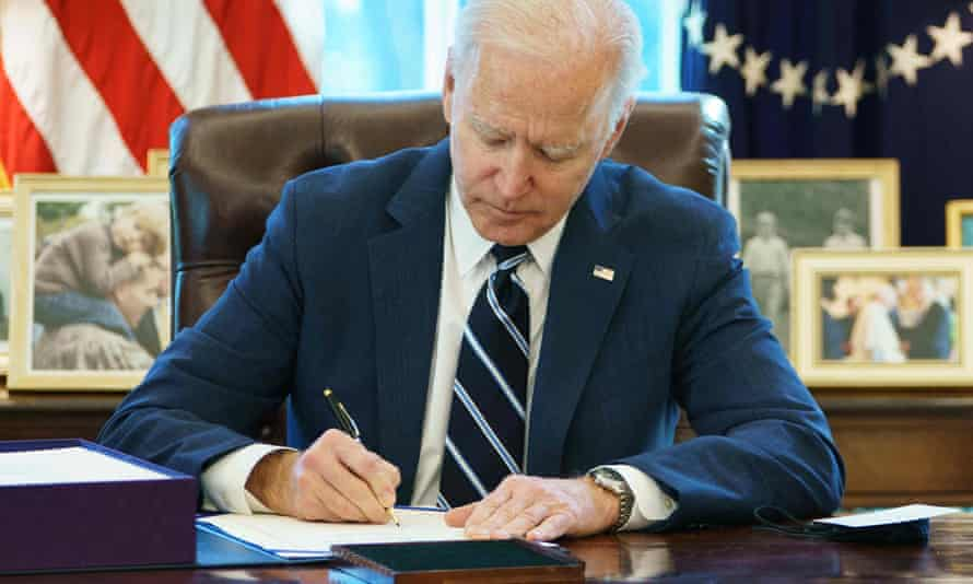 Joe Biden signs the American Rescue Plan on 11 March 11, 2021, in the Oval Office.