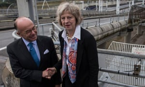 French minister of the interior Bernard Cazeneuve and his British counterpart Theresa May shake hands at the Eurotunnel terminal in Calais.