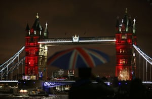 A man shelters from the rain in front of London's Tower Bridge, illuminated with blue, white and red lights as Britain expressed solidarity with France