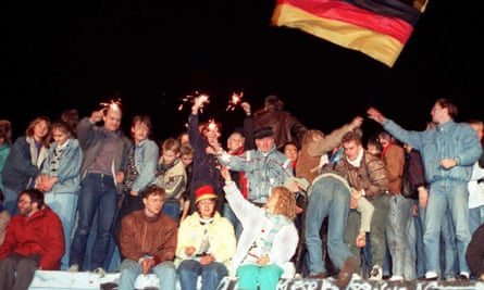 Young east Berliners celebrate on top of the Berlin Wall in 1989.