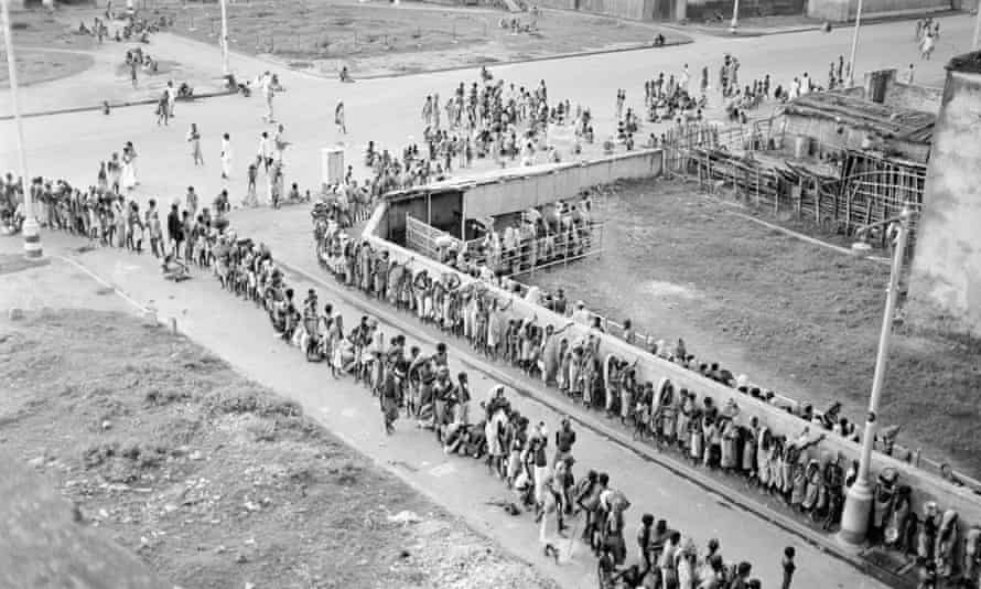 """A triple line of Indians suffering from the famine drags toward a """"soup kitchen"""" in Calcutta during the famine, circa 1943. Often, people fell dead before they could reach the food."""