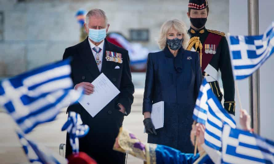 The Prince of Wales and the Duchess of Cornwall in front of rows of billowing Greek flags