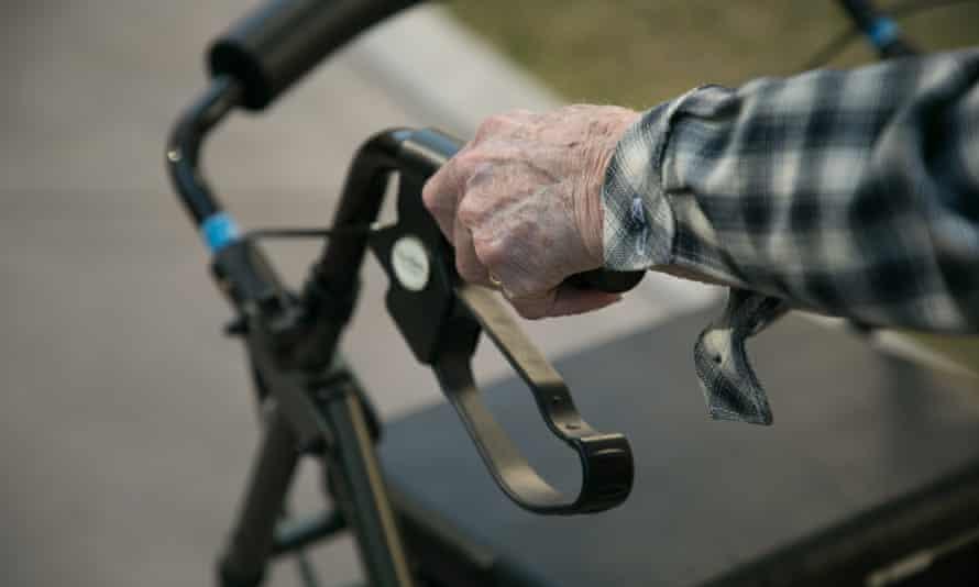 An elderly man using a walking frame