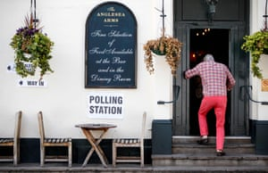 A man enters a pub, converted into a polling station, during the voting in London.