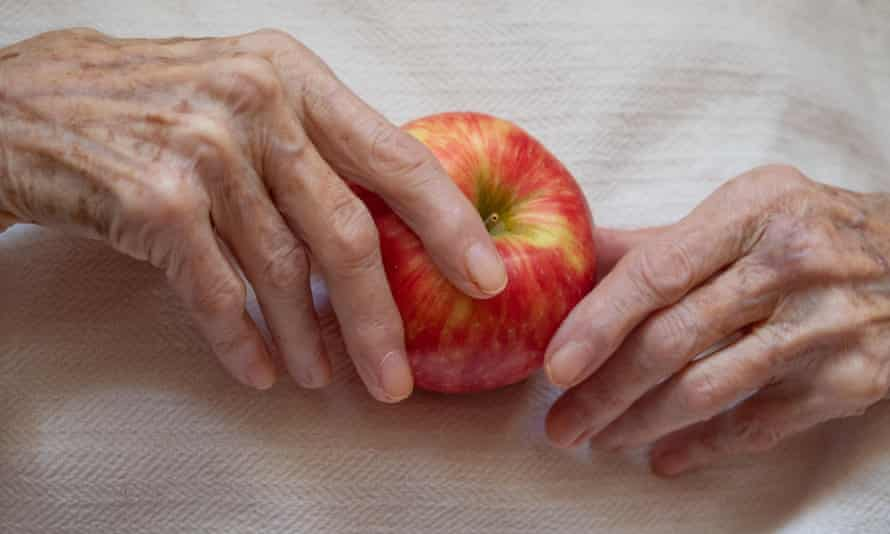 Elderly woman holding a ripe apple in her wrinkled hands against an off white background photographed from above.