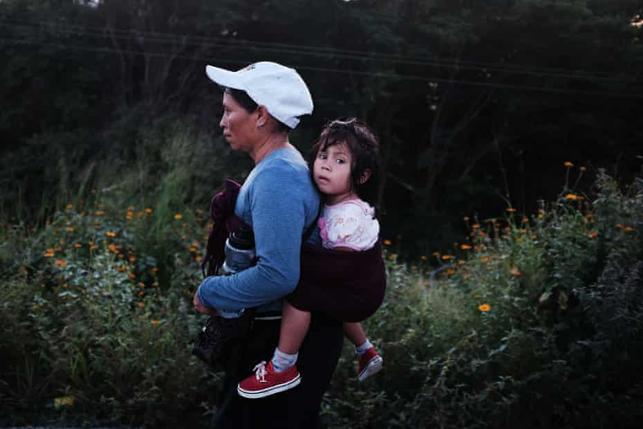 A woman and child, members of the migrant caravan travelling across Mexico, head out at dawn for their next destination.