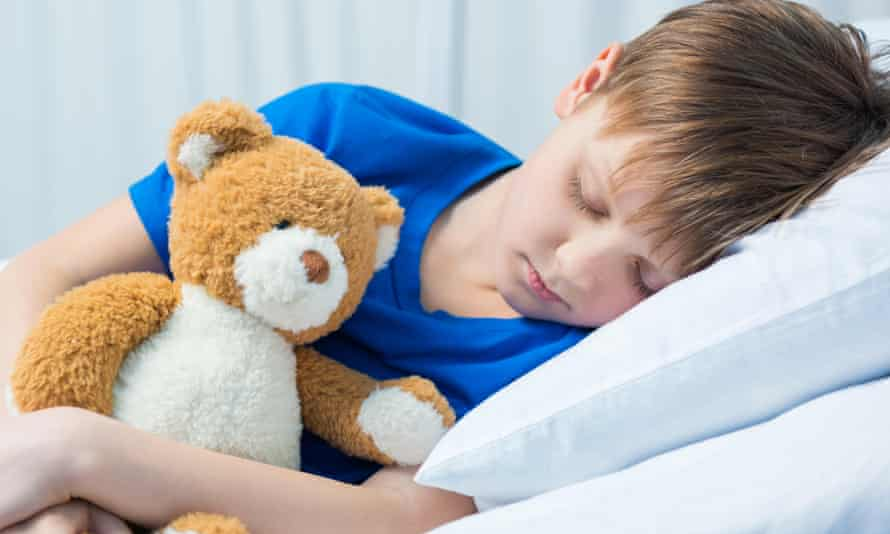 Little boy asleep in bed with teddy