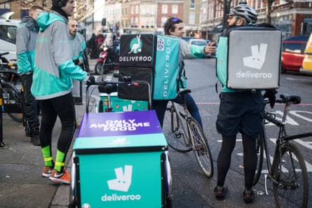 Deliveroo cycle couriers wait for orders on a London street.
