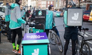 Deliveroo cycle couriers wait for orders in London.