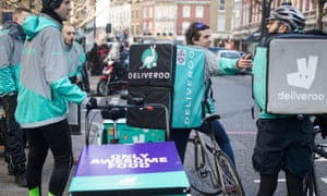 Food delivery cycle couriers chat as they wait for orders from Deliveroo.