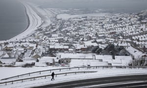 A man walks down a hill in Portland, England, after the 'mini beast from the East' on 18 March.