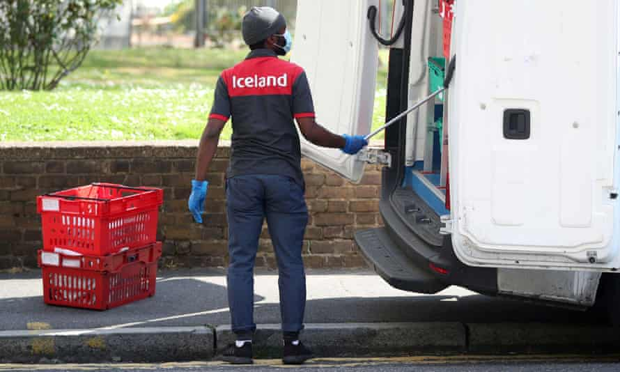 An Iceland delivery driver is seen wearing a protective face mask and gloves.